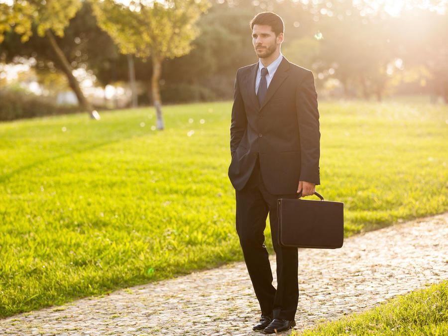 Hombre de negocios caminando por el parque