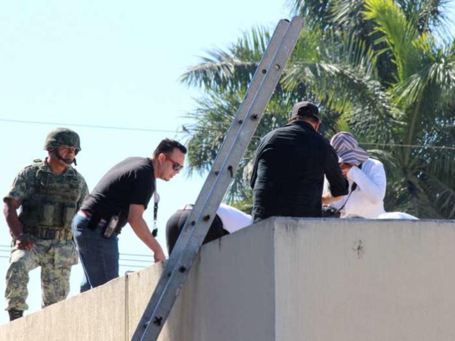 Agentes de seguridad retiran el cuerpo del techo del hospital