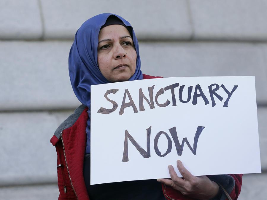 """Una mujer sostiene un letrero durante una protesta a las afueras de la Alcaldía de San Francisco en el que puede leerse: """"Santuario Ahora"""". Foto de archivo."""