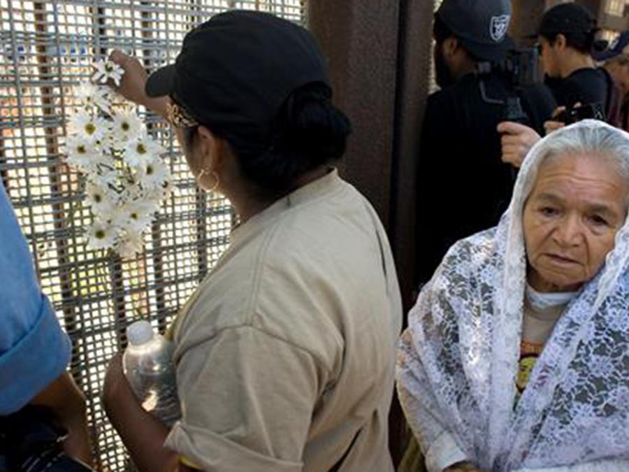 """Un miembro del colectivo """"Caravan Against Fear"""" (Caravaca contra el miedo) coloca un ramo de flores en el muro fronterizo entre EEUU y México, en San Diego."""