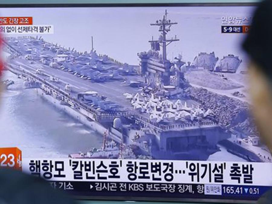Dos personas ven un programa de noticias que muestra una imagen del portaaviones estadounidense Carl Vinson en una estación de tren en Seúl, Corea del Sur.