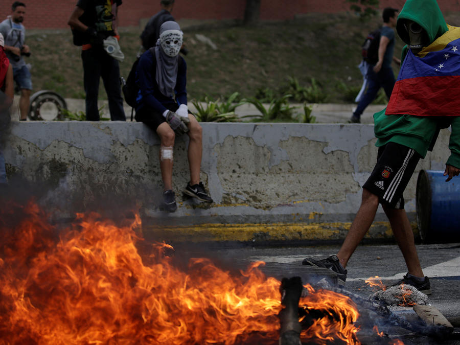 A demonstrator stands next to a fire barricade on a street during a rally against Venezuela's President Nicolas Maduro in Caracas
