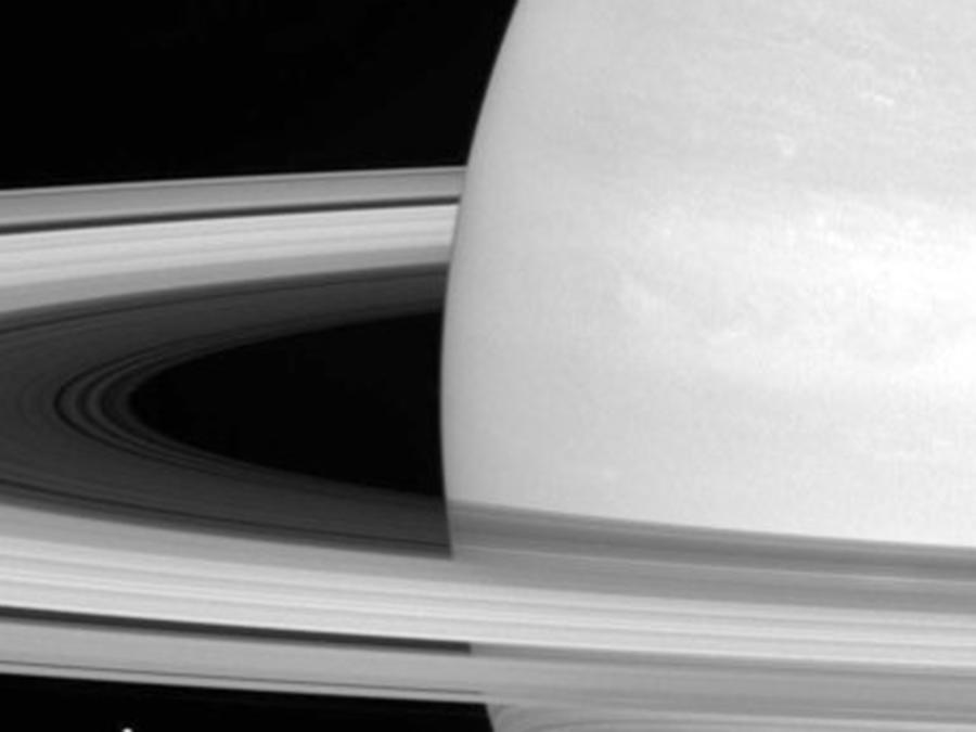 Esta foto sin fecha de la NASA muestra una de las lunas de Saturno, Mimas, empequeñecida por los anillos del planeta.