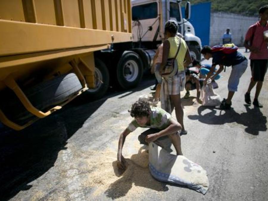 Un joven usa una funda de almohada para recoger arroz del suelo que se sacudió de un camión de carga de alimentos esperando para entrar en Puerto Cabello, Venezuela.