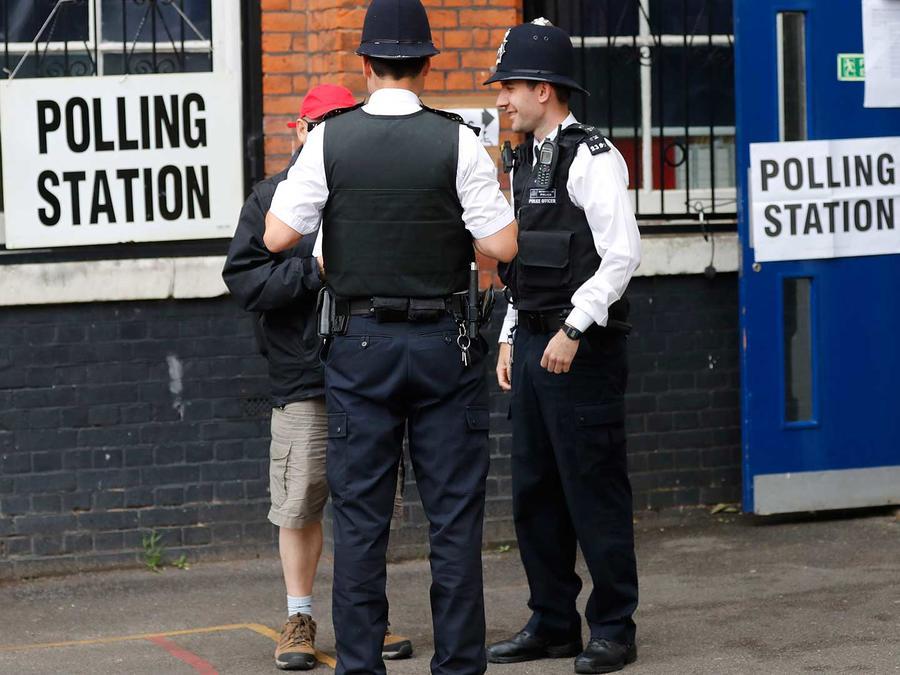 Agentes de la policía hablan con un votante en Londres