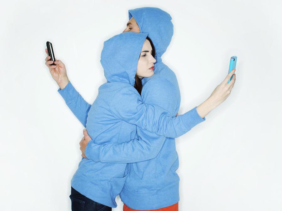Pareja abrazados y viendo su celular