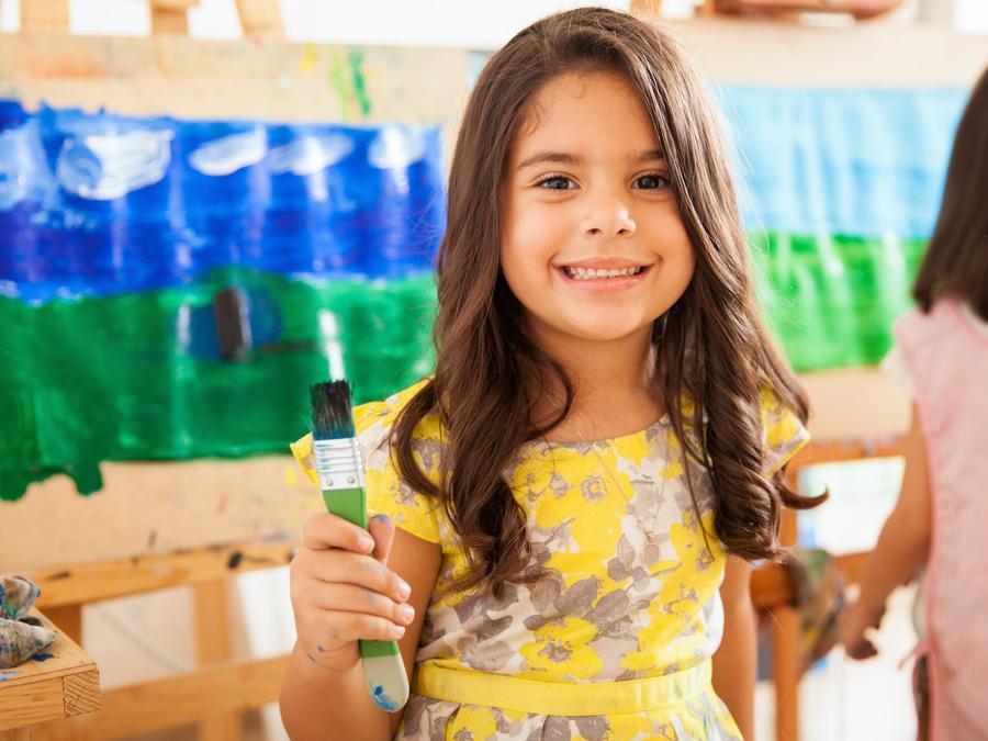 Niña pequeña con un pincel en la mano