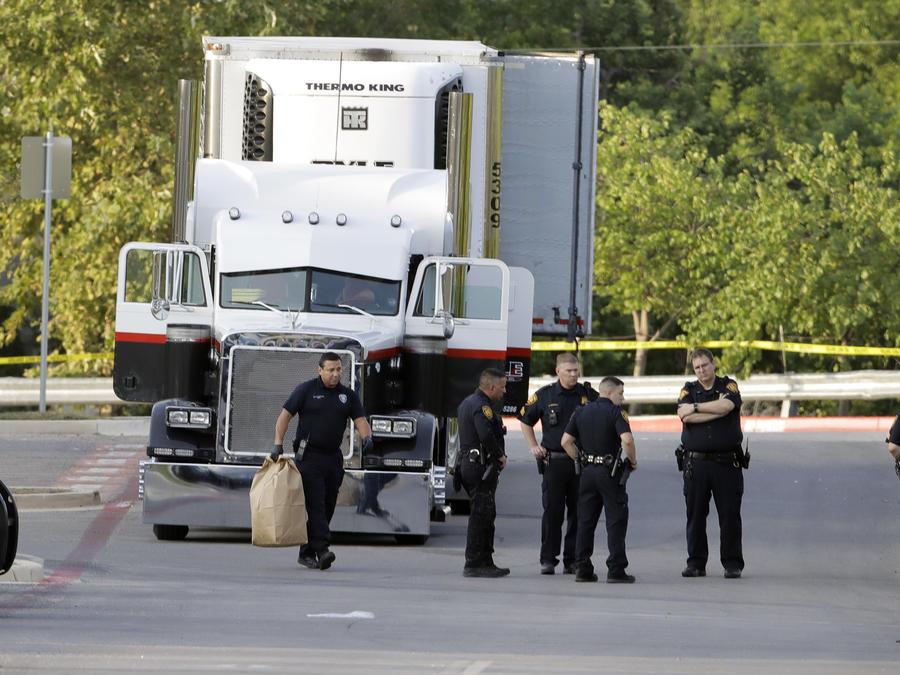Varios policías junto al remolque donde fueron halladas nueve personas muertas y al menos 30 sobrevivientes en el estacionamiento de una tienda Walmart en San Antonio, el domingo 23 de julio de 2017.