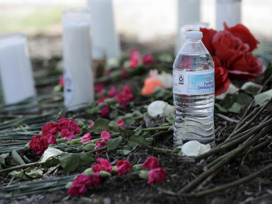 Una botella de agua, flores, velas y peluches fueron depositados en el lugar donde las autoridades descubrieronun tráiler llenos de inmigrantes afuera de un Walmart en San Antonio.