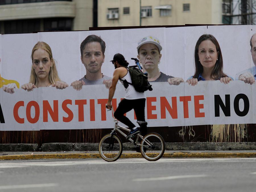 """Un hombre pasa en bicicleta en Caracas por delante de un cartel en el que puede leerse """"Esa Constituyente no va""""."""