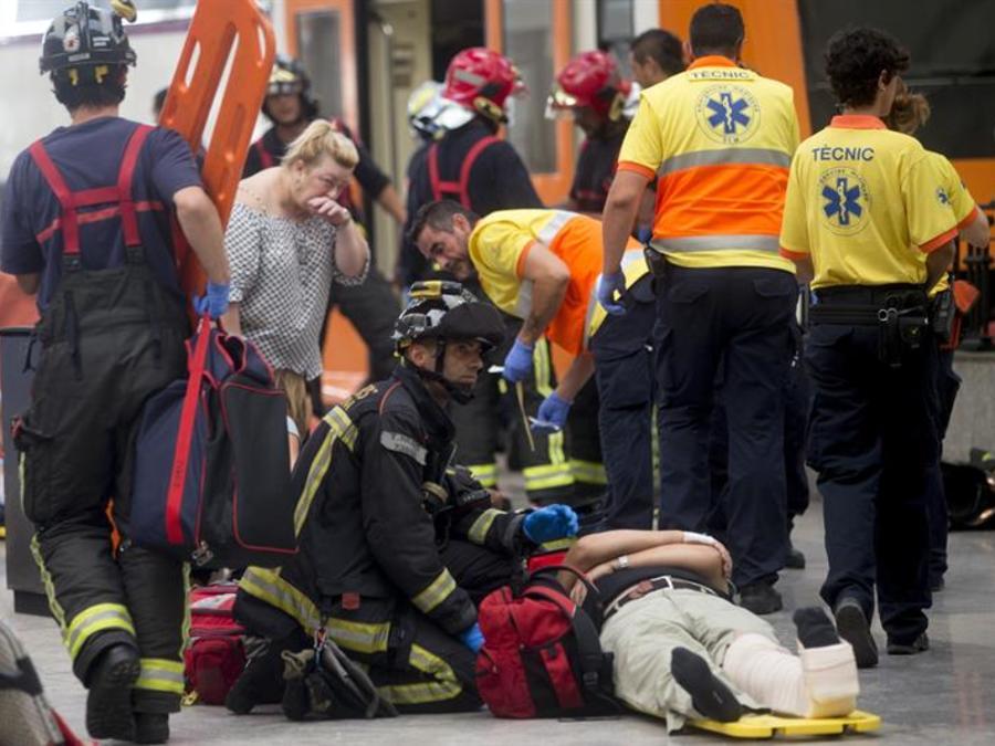 En la imagen, bomberos y servicios de emergencias atienden a los heridos del accidente de tren en Barcelona, en el que medio centenar de personas han resultado heridas.