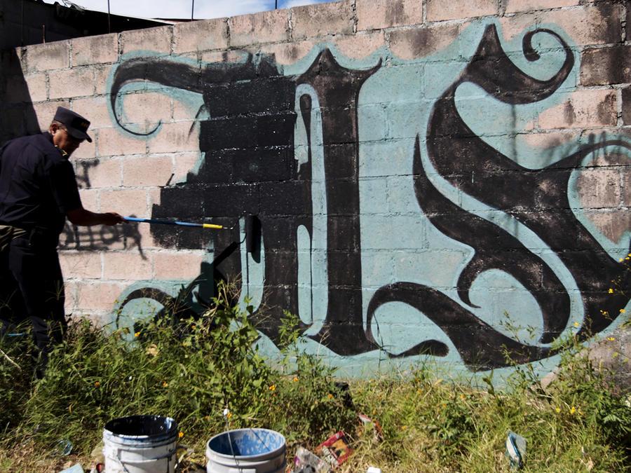 Un agente de policía pinta sobre un grafiti asociado a la Mara Salvatrucha en el barrio Mejicanos en El Salvador.