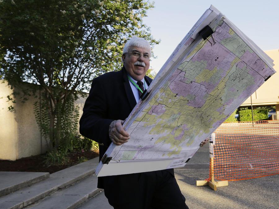 Un hombre con mapas junto a la corte de San Antonio en julio.