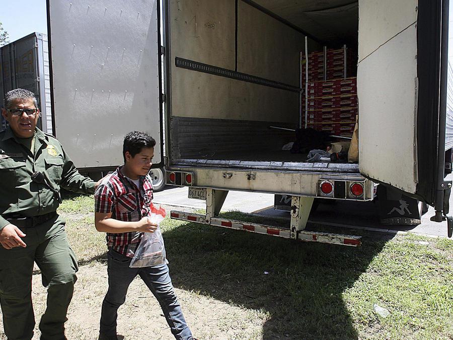 Esta foto del domingo 13 de agosto del 2017 muestra a agentes de la Patrulla Fronteriza escoltando a un inmigrante tras hallarlo dentro del remolque de un camión junto con otras personas en Edinburg, Texas.