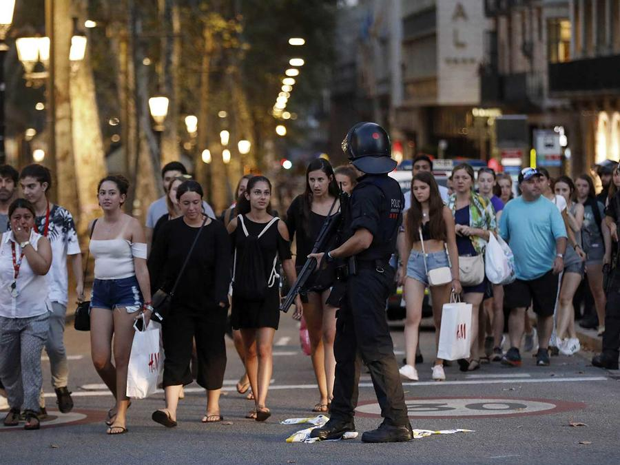 Un policía guía a peatones para que evacuen La Rambla de Barcelona donde un conductor embistió a personas con una van dejando al menos 13 muertos el 17 de agosto del 2017