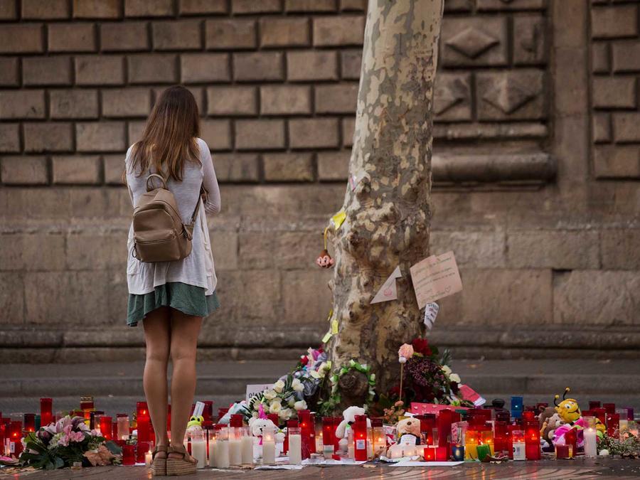 Una mujer observa un altar improvisado en La Rambla tras el ataque terrorista que dejó 14 muertos en Barcelona
