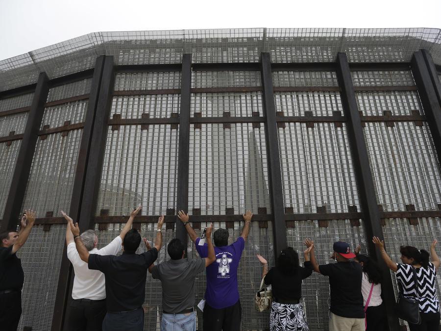ARCHIVO - En esta fotografía de archivo del 14 de julio de 2013, pastores y otras personas alzan sus brazos del lado de San Diego de una cerca en la frontera durante una ceremonia religiosa transfronteriza con otras personas del lado de la valla en Tijuan