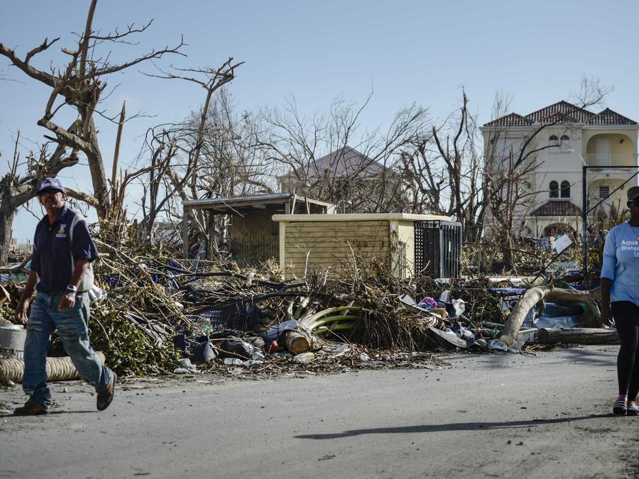 Residentes en la isla caribeña St. Martin caminan frente a casas devastadas por el huracán Irma
