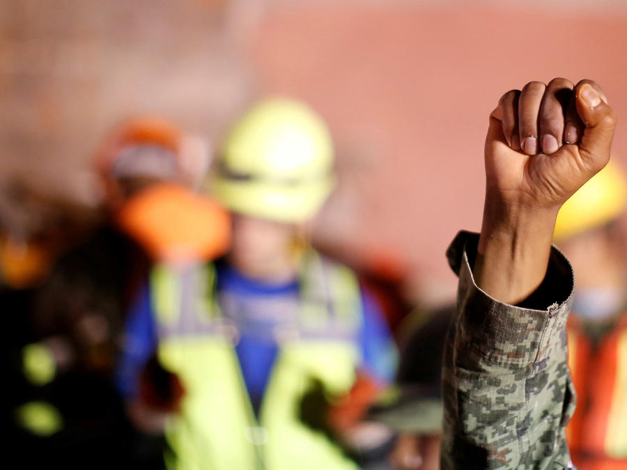 Un soldado mexicano levanta el puño pidiendo silencio mientras un equipo de rescatistas busca supervivientes en un edificio derrumbado en la colonia Condesa en Ciudad de México tras el sismo del 19 de septiembre de 2017.