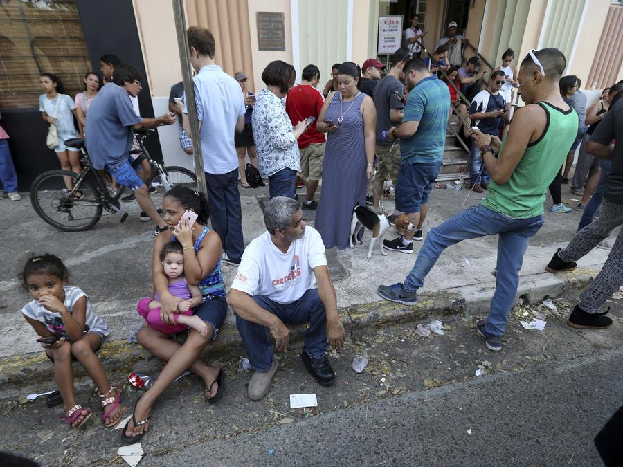 Numerosas personas intentan el domingo 24 de septiembre aprovechar una señal de internet inalámbrico en un lugar en San Juan, Puerto Rico, en su intento para comunicarse con sus seres queridos, tras el paso del huracán María