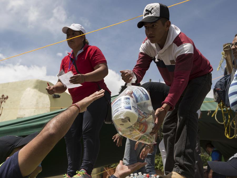 Voluntarios reciben ayuda de emergencia donada por residentes en San Gregorio Atlapulco el viernes.
