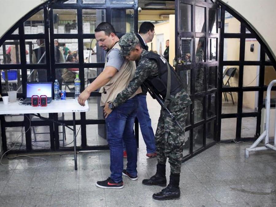 Un militar cachea a un empleado del Tribunal Supremo Electoral (TSE) de Honduras antes de entrar a la sala donde se realiza el escrutinio especial de las elecciones generales