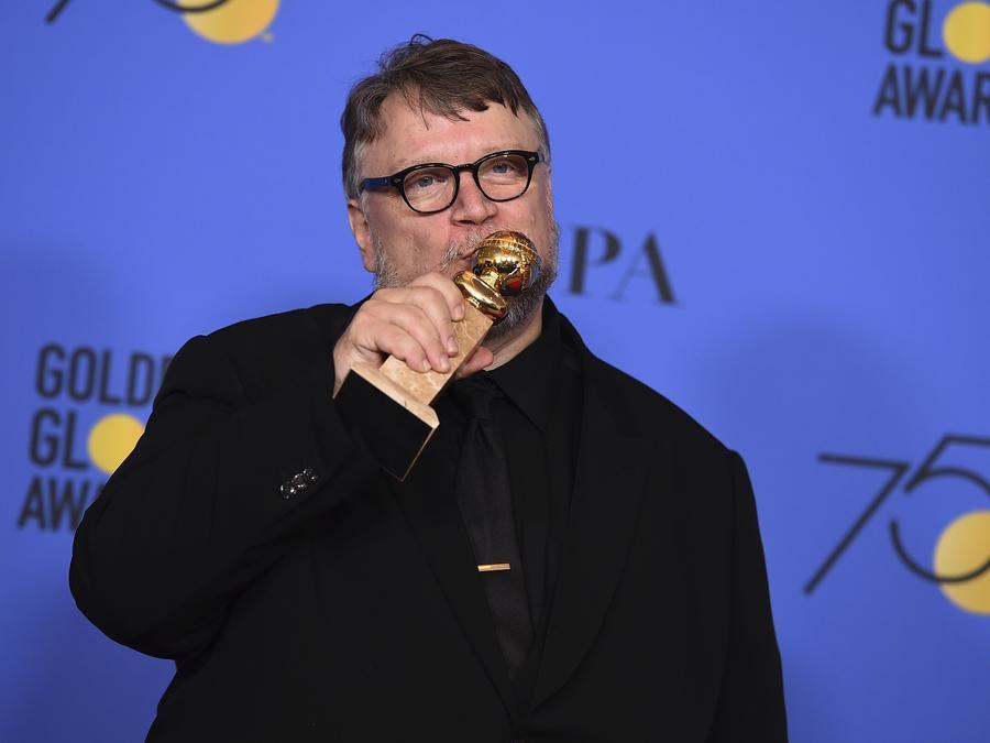 El director mexicano Guillermo del Toro besa su Globo de Oro.