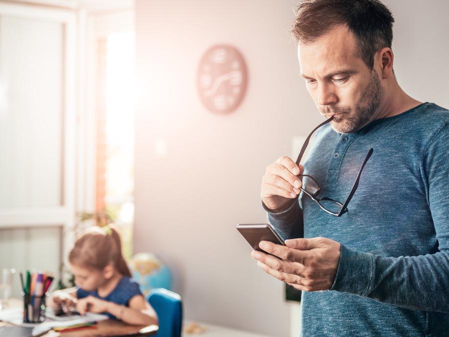 Padre mirando su teléfono móvil con hija detrás