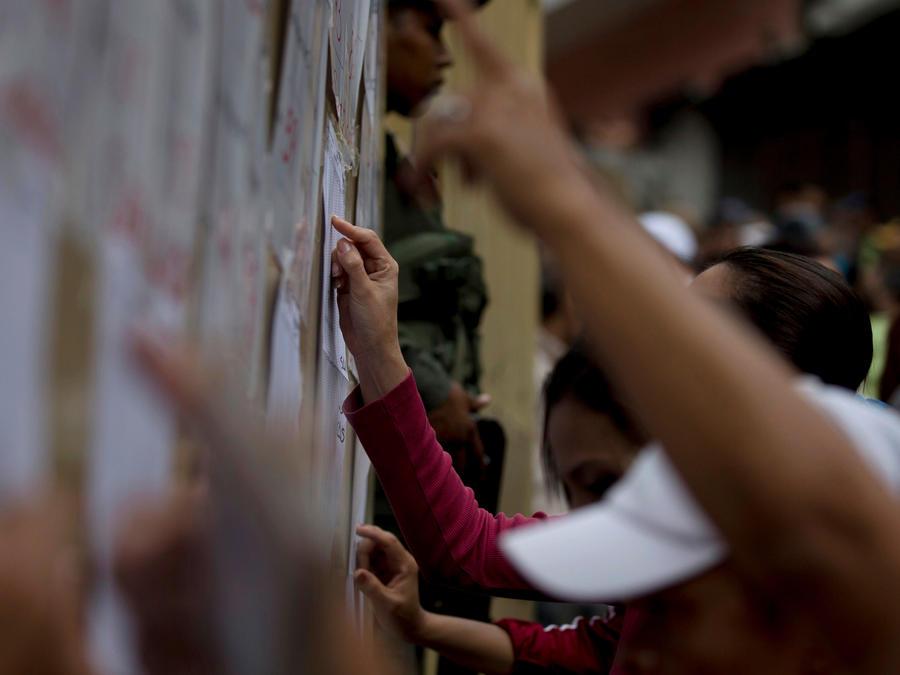 Votantes buscan listados de candidatos en Venezuela