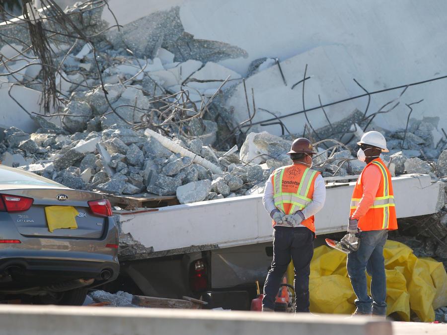 Dos obreros miran el puente que colpasó en Miami