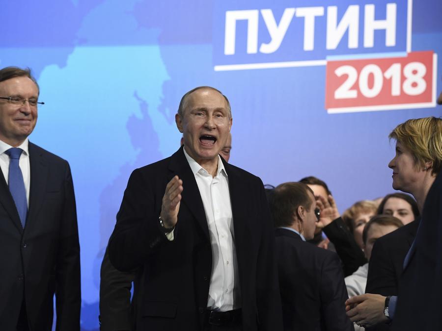 El presidente ruso Vladimir Putin, al centro, también candidato presidencial, habla en su sede de campaña en Moscú, Rusia, el domingo 18 de marzo de 2018.