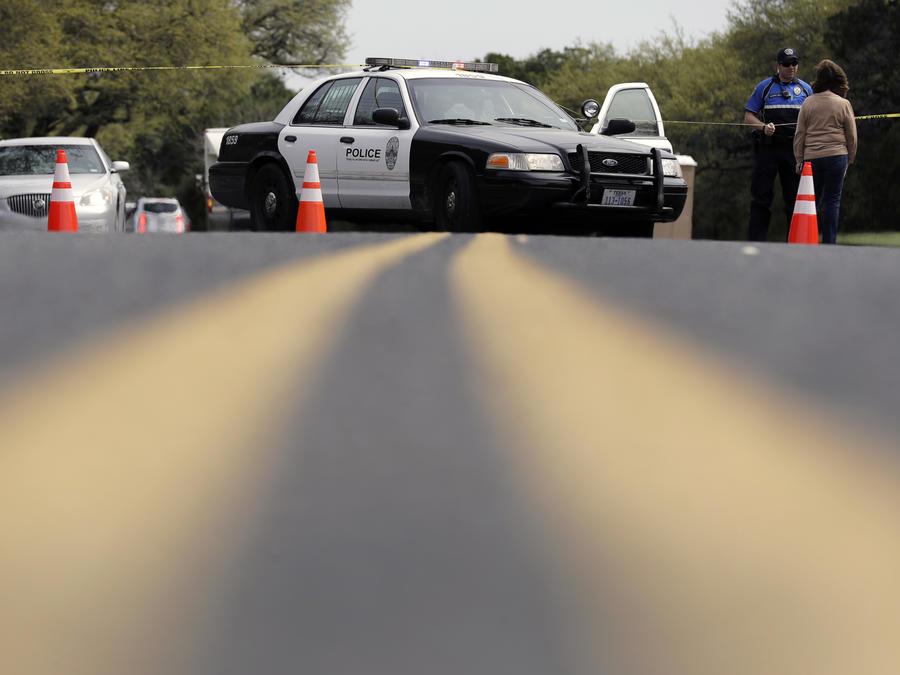 Un agente de la policía de Austin habla con una mujer en una barrera policial cerca del lugar donde se registró una explosión.