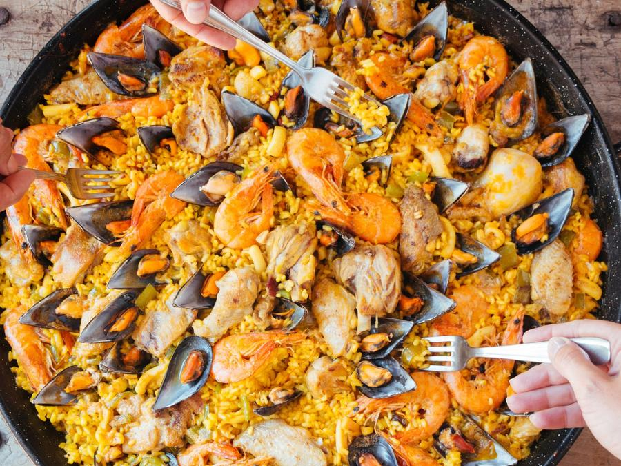 Eating paella from a large pan.