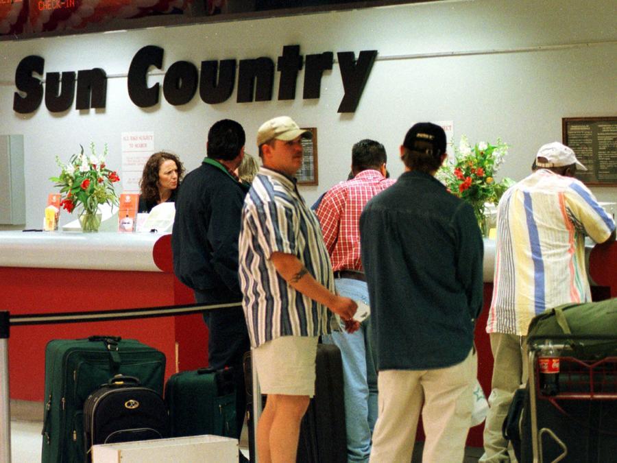 Pasajeros compran los billetes en el puesto de Sun Country.