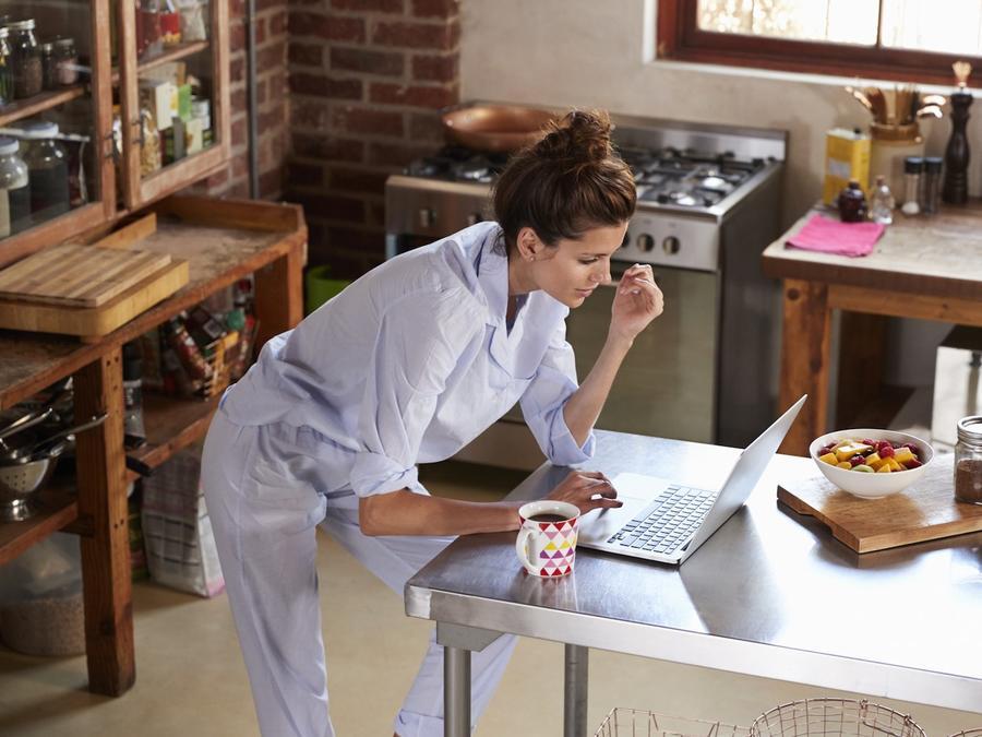 Mujer en la cocina usando computadora