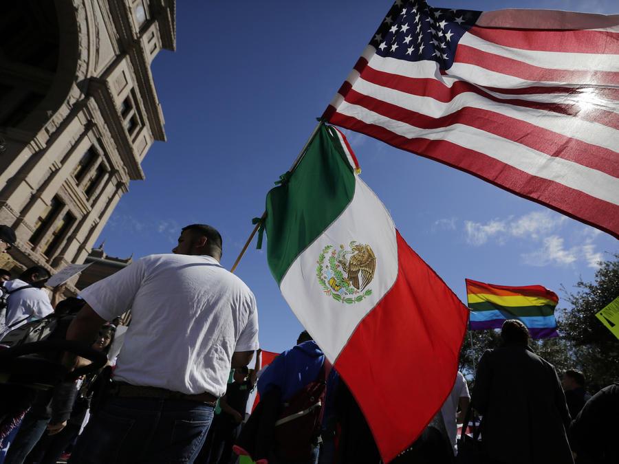 Un hombre sostiene banderas de México y Estados Unidos durante una protesta inmigrante en Austin, Texas, el 16 de febrero de 2017.