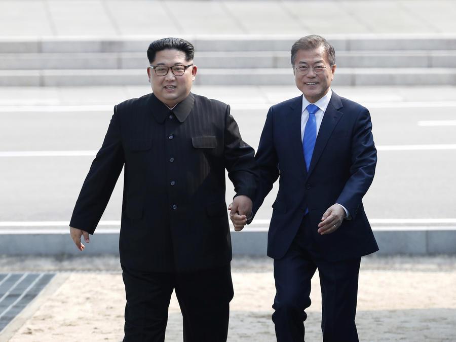 El líder de Corea del Norte Kim Jong Un, izquierda, y el presidente de Corea del Sur Moon Jae-in, derecha, cruzan la frontera al sur, este 27 de abril en el pueblo de Panmunjom, Corea.
