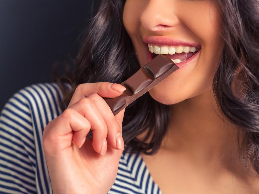 Mujer comiendo trozo de chocolate