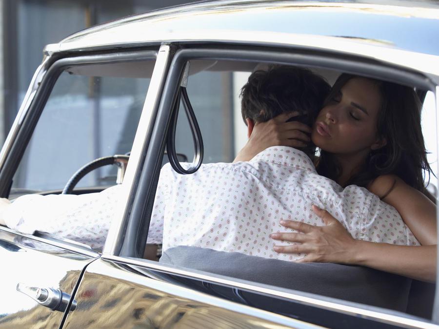 Pareja abrazada dentro de un auto