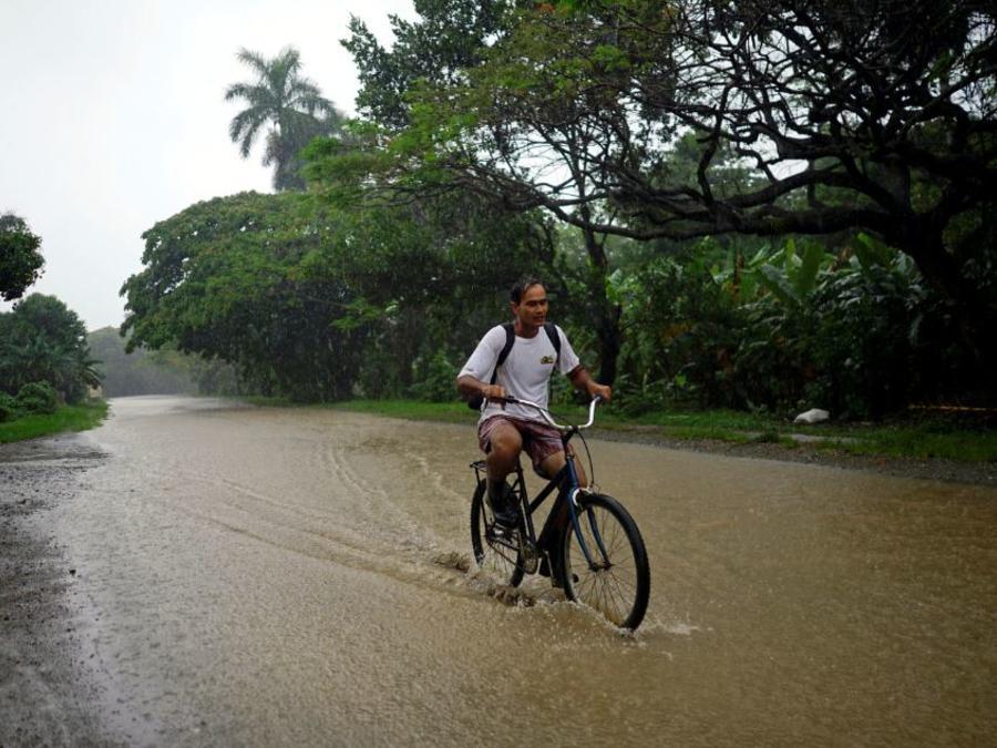 Un hombre monta una bicicleta por un camino inundado en Cuba.