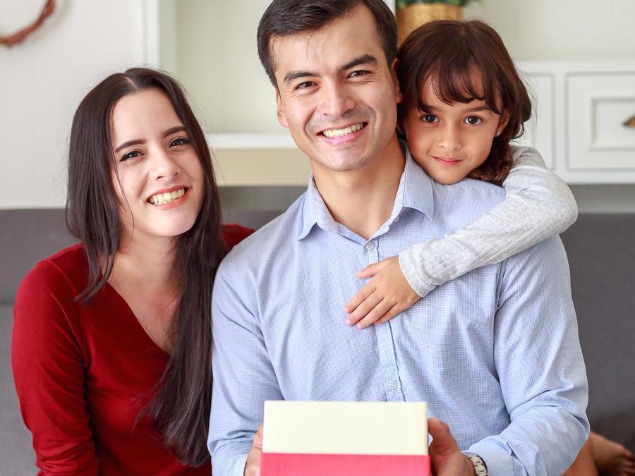 Pareja e hija con regalo para él