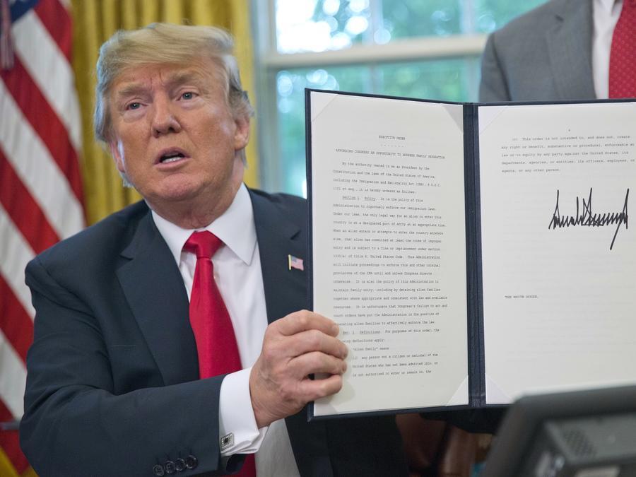 El presidente Donald Trump sostiene la orden ejecutiva que firmó para detener temporalmente la separación de famlias.