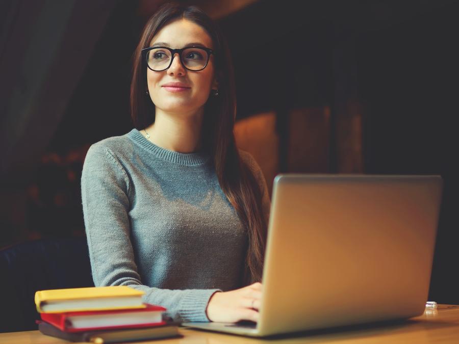 Mujer joven con computadora y libros
