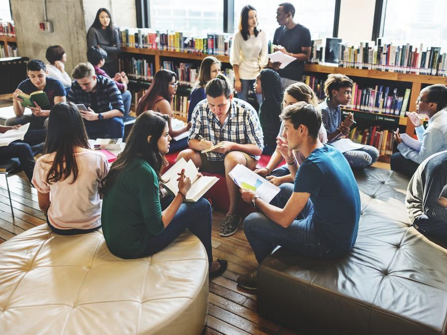 Jóvenes estudiantes de preparatoria en biblioteca