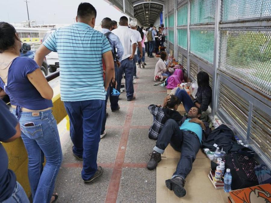 Familias migrantes en el puente que conecta con Brownsville, Texas.