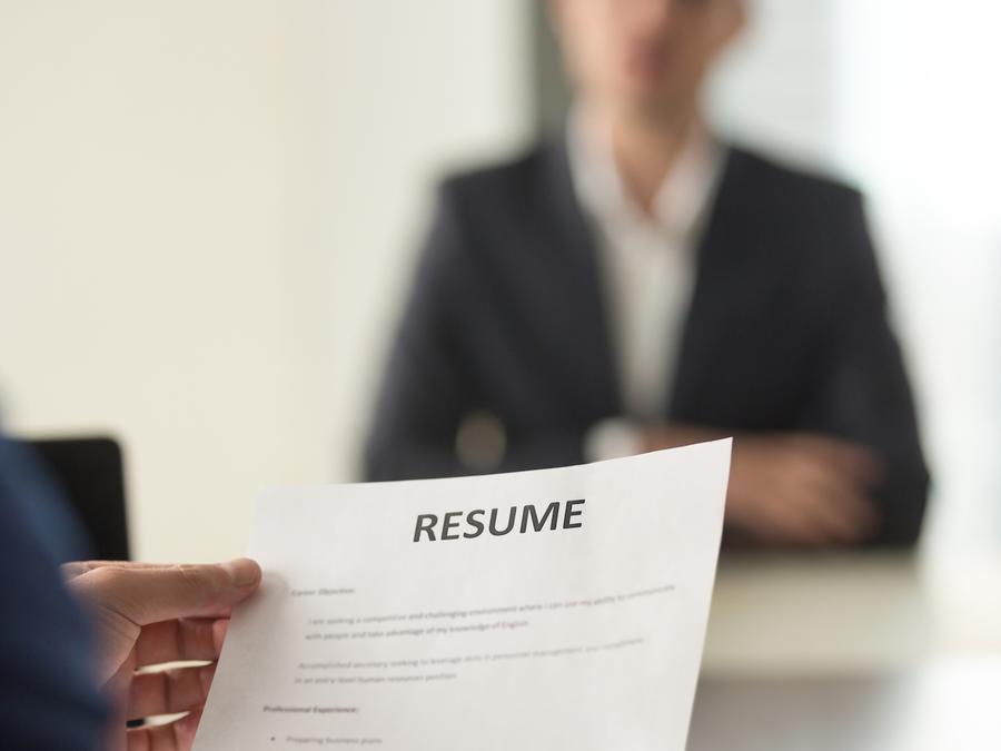 Empleador leyendo currículum en entrevista de trabajo