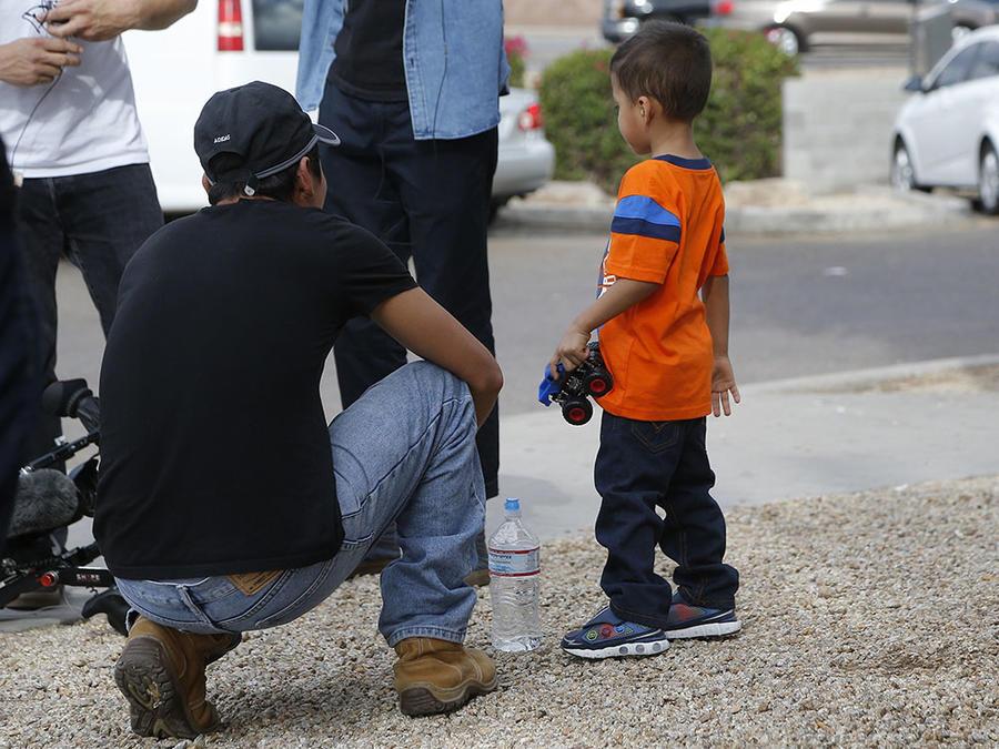 Un padre inmigrante y su hijo comparten un momento tras haberse reencontrado.