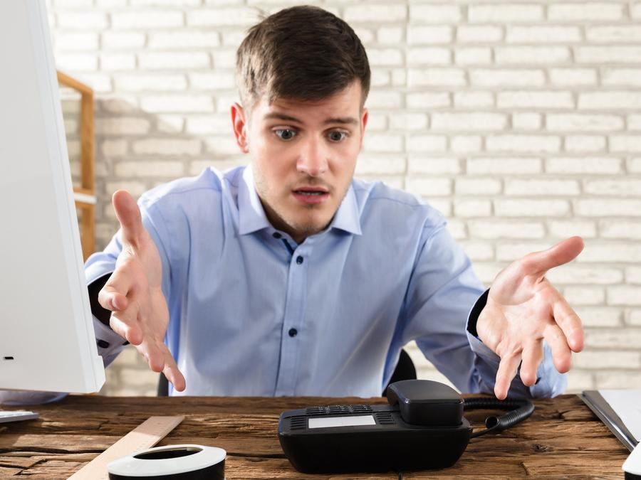 Hombre haciendo gesto impaciente ante teléfono