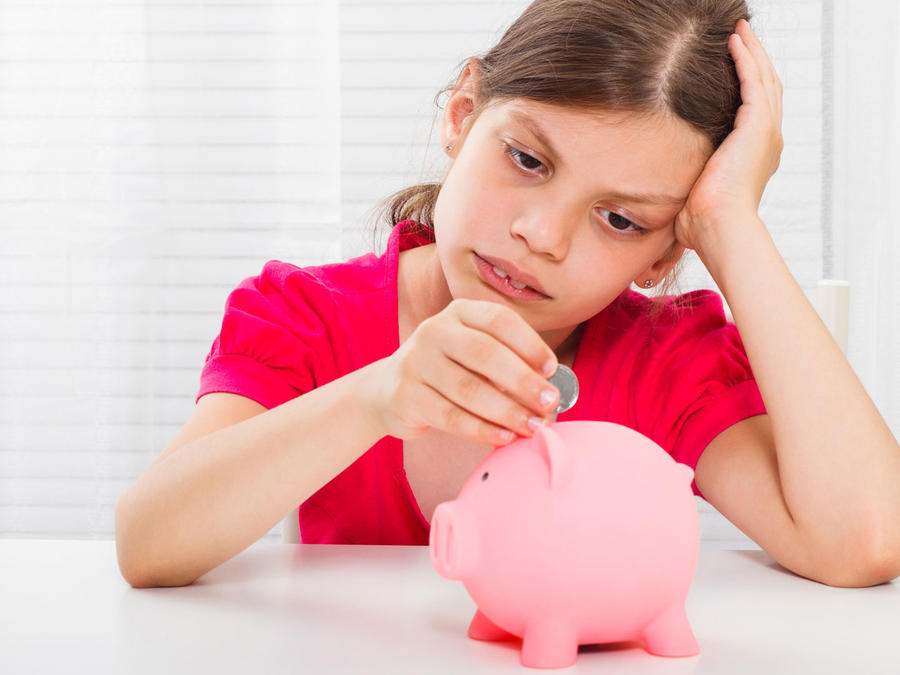 Niña disconforme poniendo dinero en una alcancía