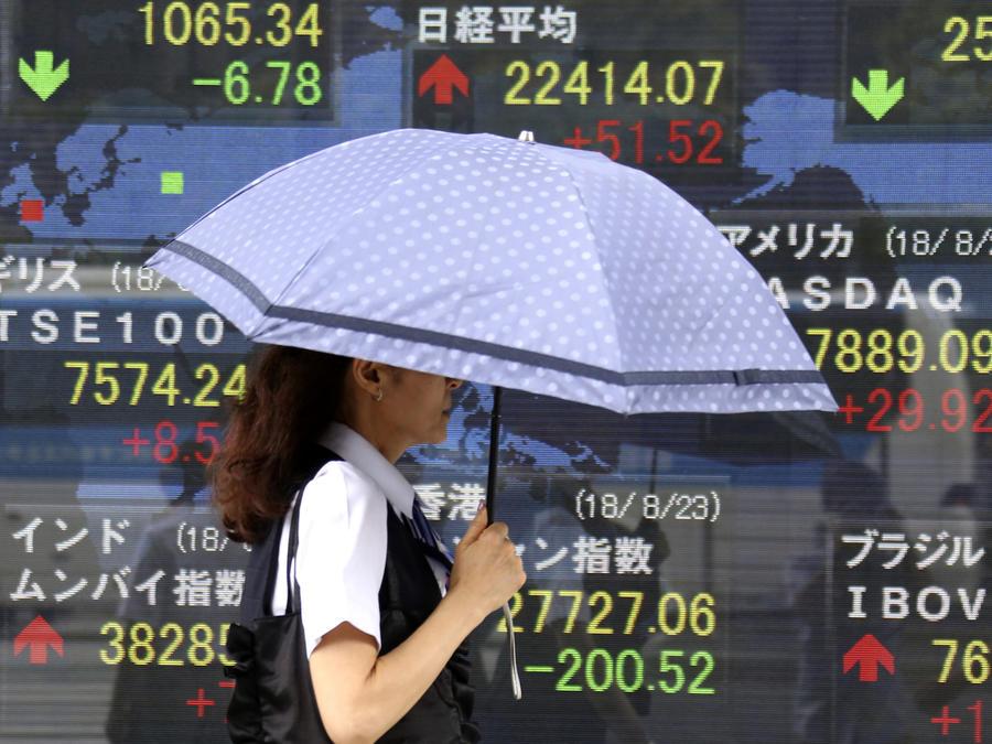Una mujer camina frente a un mural con información financiera en Japón, en una imagen de archivo de agosto de 2018.
